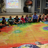 CHILDREN SITTING ON MAP OF MARS